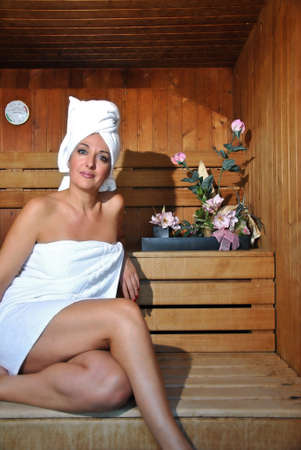 woman lying down: woman relaxing in a sauna with the heat
