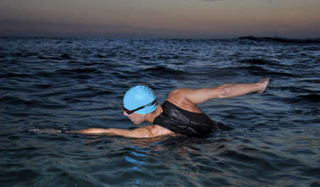 young athlete triathlon swimming in the sea while dawns