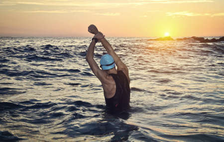 young athlete triathlon in front of a sunrise over the sea Standard-Bild
