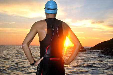 swimming competition: young athlete triathlon in front of a sunrise over the sea Stock Photo