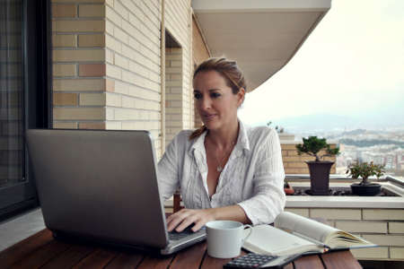 woman working quietly on your terrace with a coffee Standard-Bild