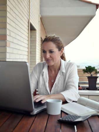 woman working quietly on your terrace with a coffee Stock Photo