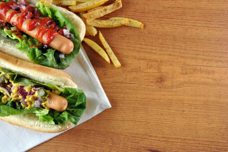 two hot dogs with salad, onions and sauce