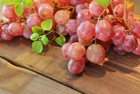 red grapes with green leaves on wooden table photo