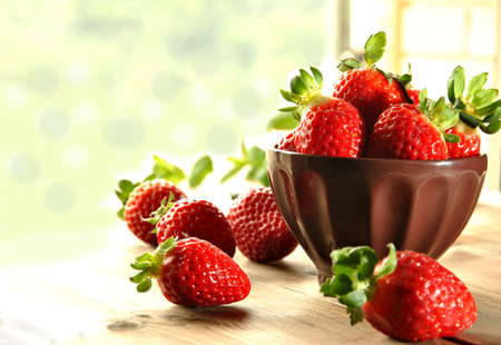 Fresh strawberries on a plate and brown fabric photo
