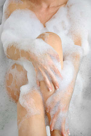 Woman bathing with a lot of foam in her bathtub photo
