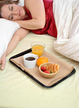 woman sleeping on her bed with a breakfast at his side photo