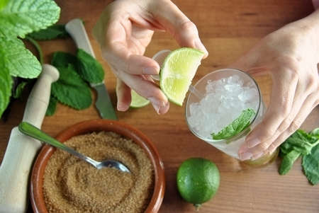hands preparing mojito cocktail with limes and mint Standard-Bild