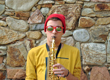 modern musician posing with his saxophone in the garden photo
