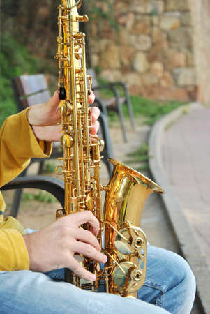 african sax: modern musician posing with his saxophone in the beach