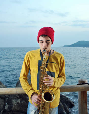 modern musician posing with his saxophone in the beach photo