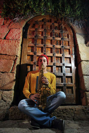 musician with his saxophone sitting on a medieval gate photo