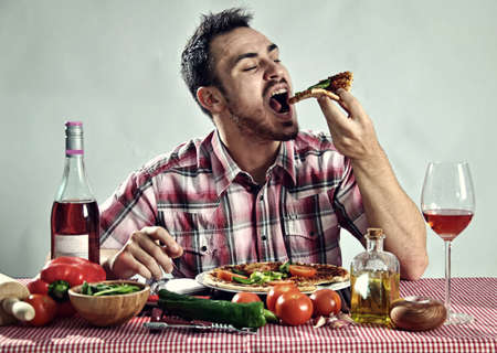 Crazy hungry man eating pizza in a restaurant