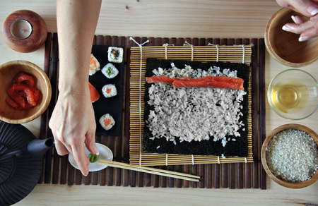SUSHI: hands cooking sushi with rice, salmon and nori