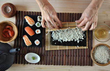 sushi restaurant: hands cooking sushi with rice, salmon and nori