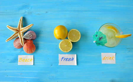 Fresh lemonade with starfish and seashells on blue table photo