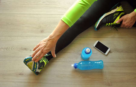 runners: runner legs stretched on wooden floor with isotonic drink Stock Photo