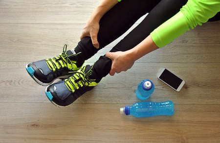 runner legs stretched on wooden floor with isotonic drink Standard-Bild