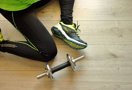 isotonic: runner legs stretched on wooden floor with isotonic drink Stock Photo