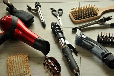 black hair: herramientas de peluquería como secadores, tijeras y peines en un piso de madera Foto de archivo