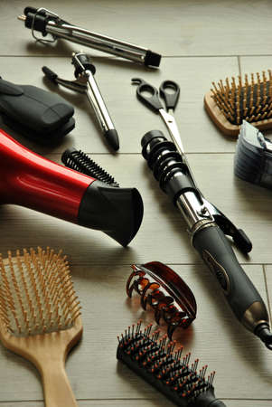 hairdressing tools like dryers, scissors and combs on a wooden floor