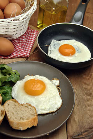 oilcan: Fried eggs with plate, bread, and oilcan on a wood table Stock Photo