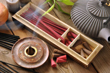 VARIOUS TYPES OF INCENSE WITH TEAPOT AND BUDDHA STATUE Stock Photo