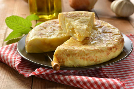 Spanish omelette with potato and egg, accompanied by olive oil Foto de archivo