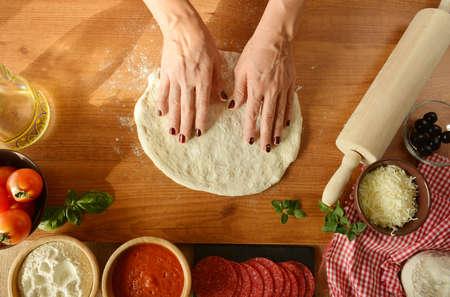 Frau Hände kochen Pizza zu Hause, das Hinzufügen alle Zutaten