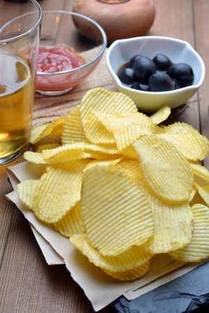 accompanied: snack chips and beer accompanied by olives