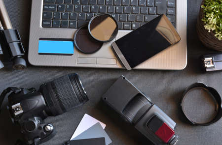 desktop with photography equipment, camera, tripod,flash  and computer
