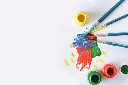 yellow paper: watercolors and brushes with childrens drawings on white canvas