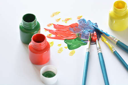 tempera: watercolors and brushes with childrens drawings on white canvas
