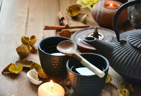 accompanied: cups of black tea accompanied by incense , cinnamon and candles
