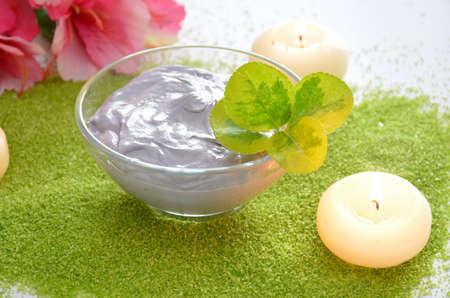cremas faciales: crema especial para el tratamiento corporal con velas aromáticas Foto de archivo