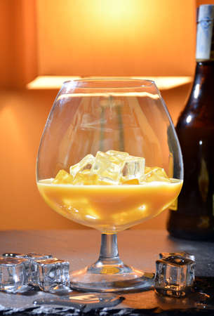 baileys: splash of Irish Cream liqueur accompanied by a glass of ice. cold alcoholic beverage to drink at home