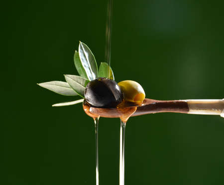 Olive oil falling on two olive with olive leaves to flavor a Mediterranean salad .