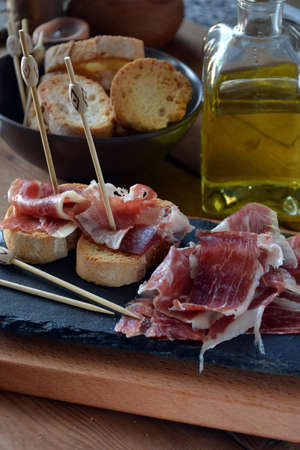 serrano: appetizer of ham Serrano with bread roasted and accompanied by a glass of wine