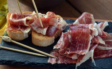 pan y vino: aperitivo de jamón serrano con pan tostado y acompañado de una copa de vino
