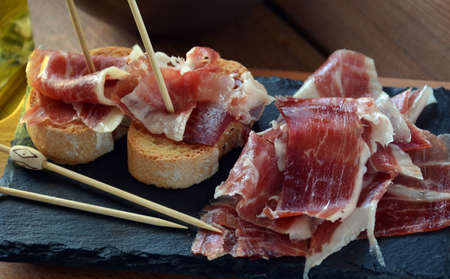 appetizer of ham Serrano with bread roasted and accompanied by a glass of wine