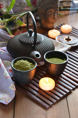 taza de te: cups filled with Japanese tea kettle of hot water and incense and candles
