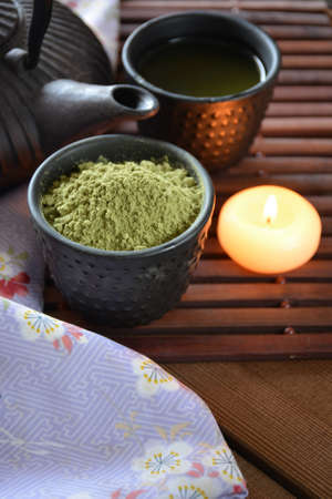 green powder: cups filled with Japanese tea kettle of hot water and incense and candles