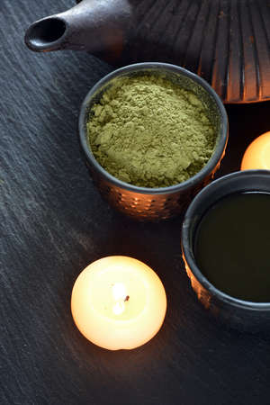 green and black: cups filled with Japanese tea kettle of hot water and incense and candles