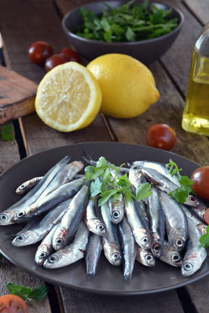 accompanied: fresh anchovies, placed on a wooden table and accompanied by oil, tomatoes and parsley
