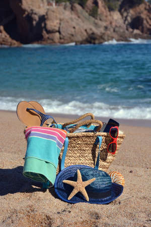 accompanied: Beach bag with a book and a telephone and sunglasses accompanied by a sea star