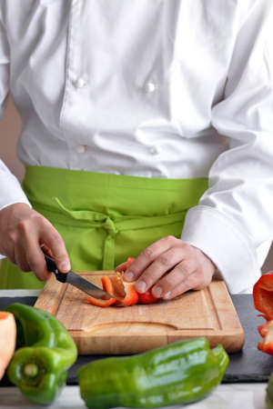 Chef cutting vegetables at the table for cooking