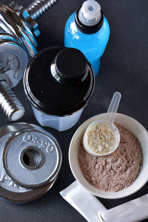 whey: Whey protein taste vanilla and chocolate, dumbbell back to start training Stock Photo