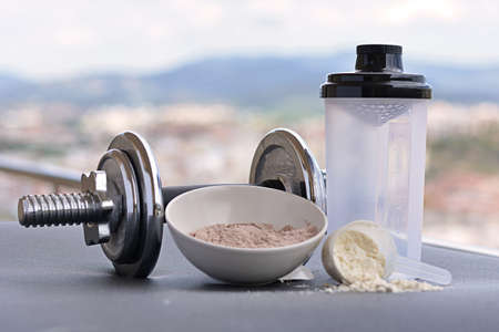 Whey protein taste vanilla and chocolate, dumbbell back to start training Standard-Bild