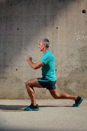 Elderly man practicing sports on the street Standard-Bild