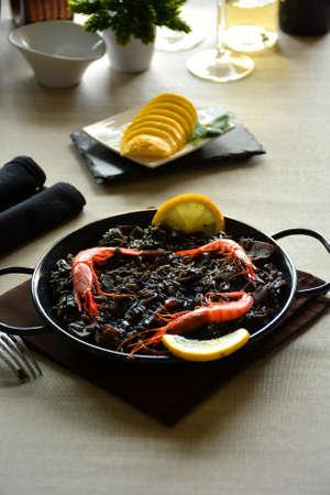 paella of rice black with Squid, accompanied of wine white Stock Photo